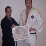 Sensei Nicholls presents Sempai Simon Irwin with Shodan.